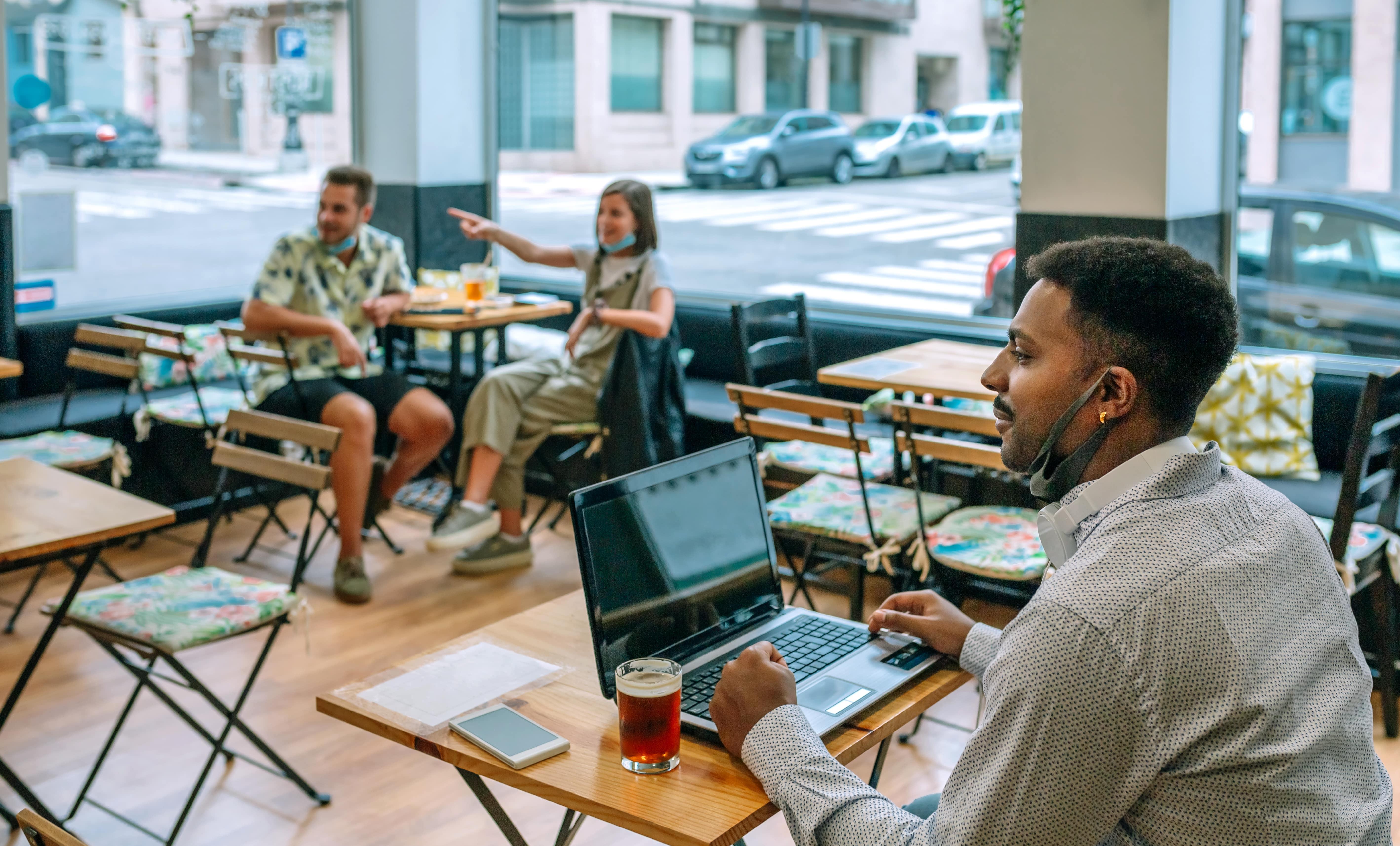 man-teleworking-with-laptop-in-coffee-shop-UAGRDRA-min