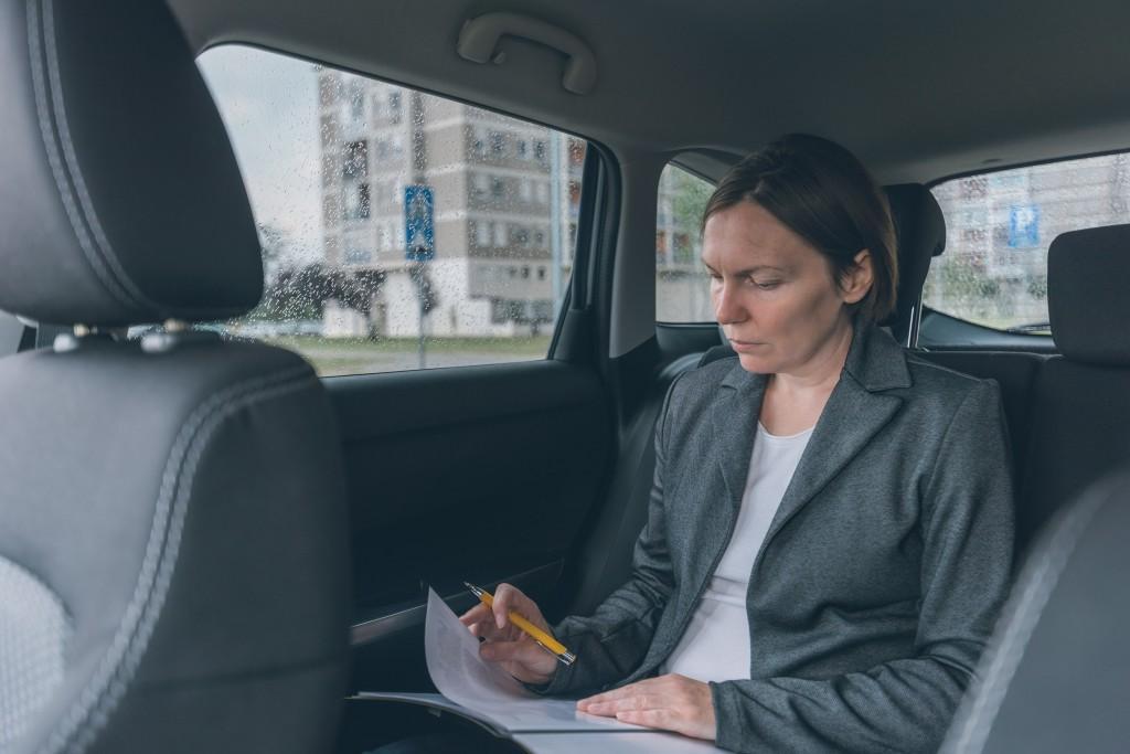 businesswoman-doing-business-paperwork-on-car-back-DHBNHHR-min